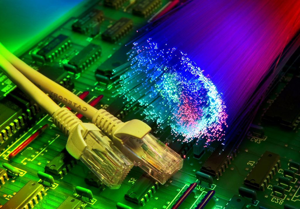 electronic printed circuit board with network cable closeup on fiber optical background